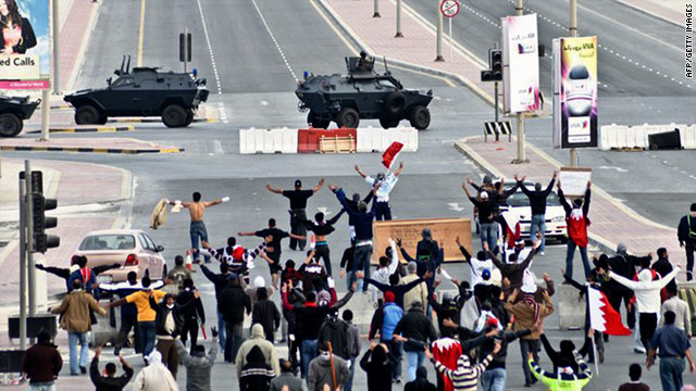 Anti-government protestors in front of military vehicles near Pearl Square in Bahraini capital Manama on March 16.