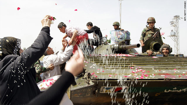 Syrian women shower troops with petals and rice as they pull out of the  protest hub of Daraa on May 5 after a military lockdown.