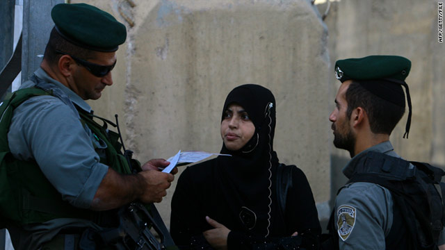 An Israeli border guard checks the ID of a Palestinian woman at a checkpoint on the outskirts of Bethlehem in August 2010.