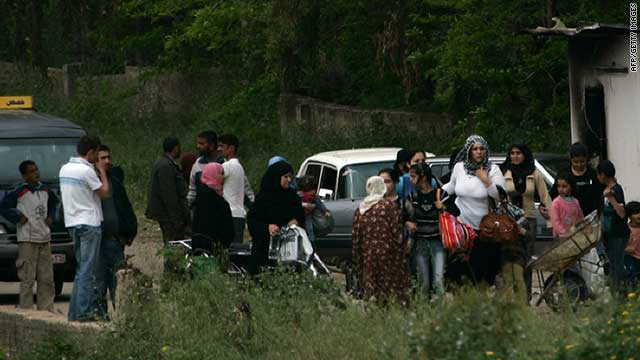 Syrians flee on foot on April 28, 2011 into northern Lebanon after they said unrest broke out in the Syrian town of Tall Kalakh.