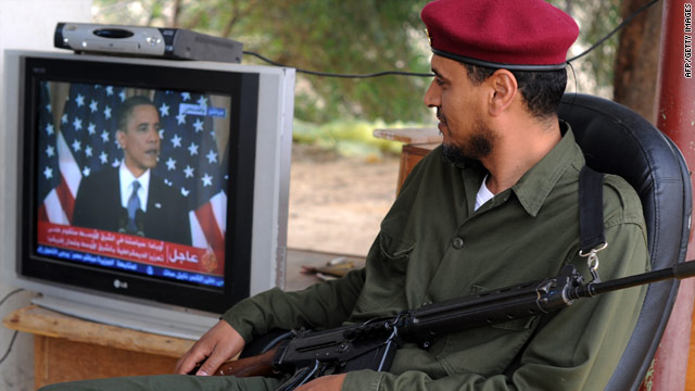A rebel fighter watches U.S. President Barack Obama's speech on TV in the eastern Libyan town of Zuwaytinah.