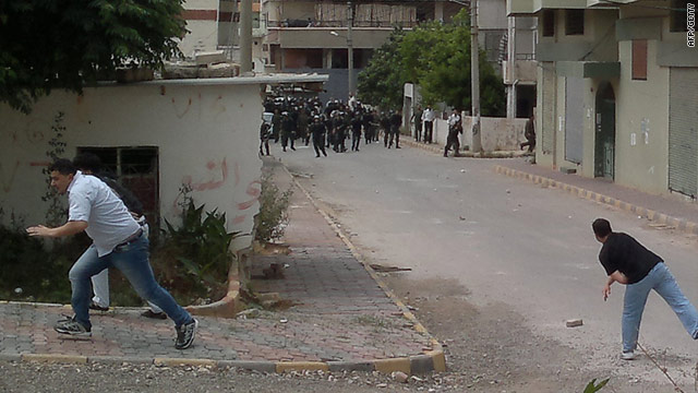 Men throw stones at Syrian riot police during clashes in the coastal town of Banias on Friday, May 27.