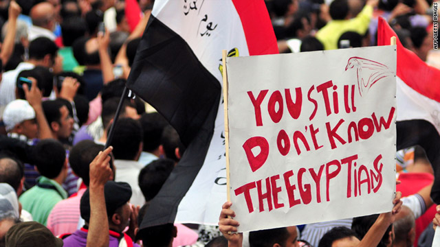 Egyptians crowd the streets, holding signs and waving the national flag, during a protest in Alexandria, Egypt, on Friday.