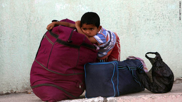 A Palestinian boy waits to cross the border from Gaza to Egypt with his family on Saturday.