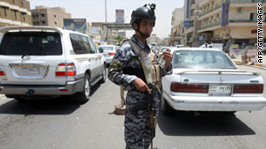 An Iraqi police officer works at a checkpoint in Baghdad, a day after five U.S. soldiers were killed.