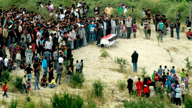 Syrian mourners gather at a funeral service for an anti-regime protester on the border with Turkey on Saturday.