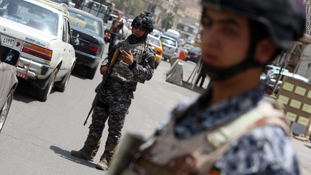 Iraqi policemen man a checkpoint after blasts in June killed five U.S. soldiers. Moday's attacks have reportedly killed a further two.