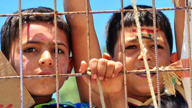 Syrian boys stand behind a fence at the Turkish Red Crescent camp Friday, 30 kilometers from the Syrian border.