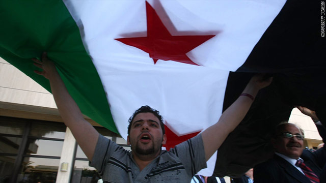 A member of Syrian opposition shouts slogans under a former Syrian flag to protest against President Bashar al-Assad.