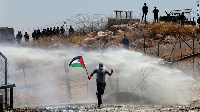 A protester runs through tear gas during a demonstration last week against a barrier in the West Bank town of Bilin.