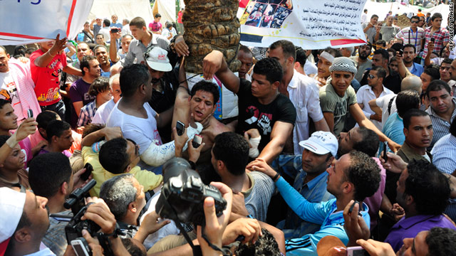 Protesters surround a man alleged to be one of several armed men who tried to attack them in Cairo's Tahrir Square on Tuesday.