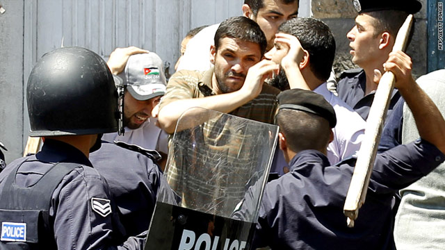Riot police beat protesters with sticks Friday on the streets of Amman, Jordan.