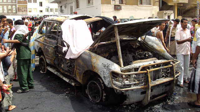 Yemenis look at a destroyed vehicle following a car bomb that killed a British man in Aden, Yemen, on July 20.