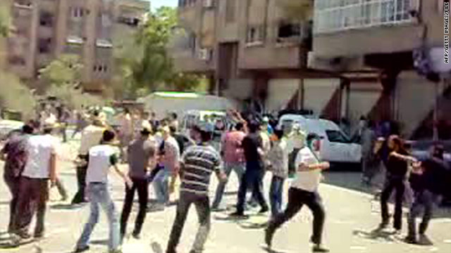 A YouTube image from July 15 shows Syrian anti-government protesters running for cover from security forces in Damascus.