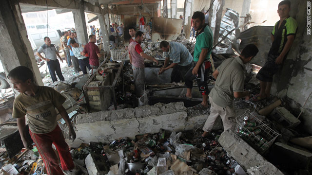 Iraqis walk through a decimated liquor store after a car bombing (Photo courtesy of CNN).