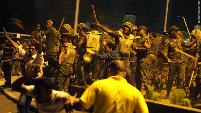 Egyptian military police react as some demonstrators throw stones and water bottles during a protest at Cairo's Tahrir Square on August 12.