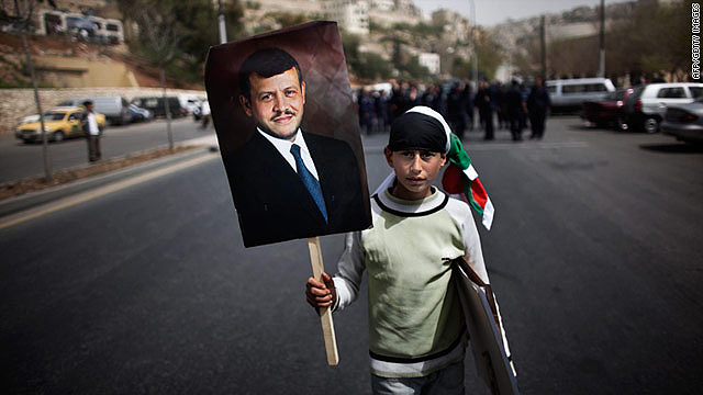 A young Jordanian parades with a portrait of King Abdullah II during a pro-government demonstration in Amman on April 1, 2011.