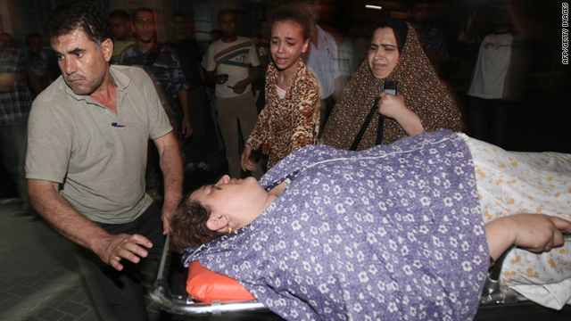 Palestinians wheel a wounded woman Tuesday following an attack in Gaza City.