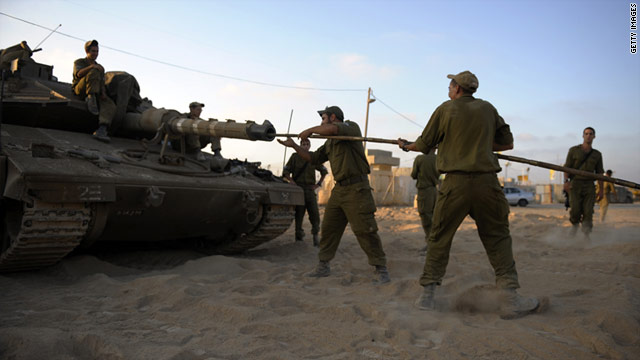 Israeli soldiers clean the barrel of a tank near the southern kibuttz of Nahal Oz on the border of the Gaza Strip.