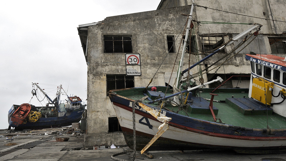 Boats lie next to a building in Talcahuano on Monday after they were taken ashore by a tsunami caused by the earthquake. (AFP/Getty Images)