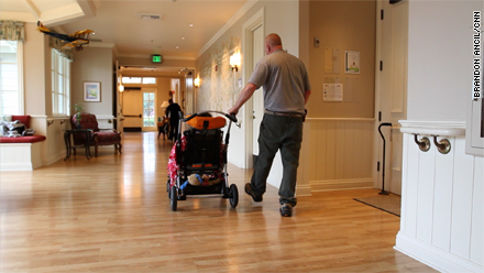 Volunteer George Warren wheels a young patient through George Mark.