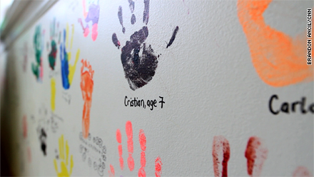 Handprints of former patients and family members at the George Mark house decorate an activity room wall.