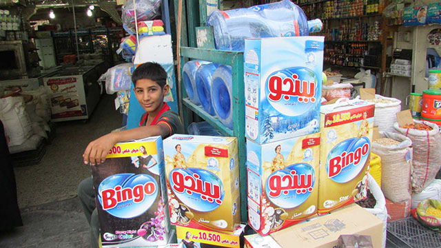 Khair, 12, takes a break from helping a family friend stock shelves at a store at the Karrada market in central Baghdad.