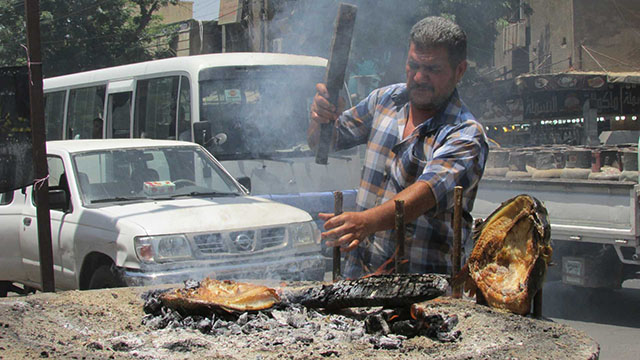 A vendor cooks Masouf, a traditional Iraqi dish of grilled carp, on an open pit at the Karrada market in central Baghdad. The fish is cut open, flattened and slow cooked.