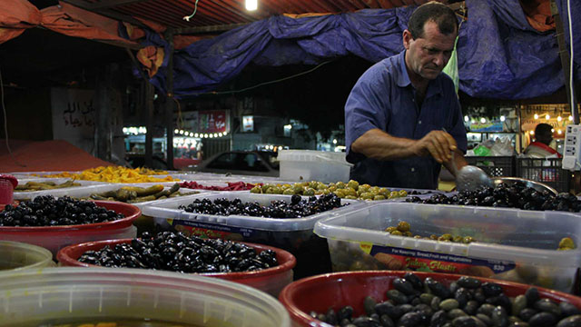 A vendor scoops up Turkish olives from a tub for a customer. The vendor sells olives and pickles from Iraq, Syria, Turkey and Greece.