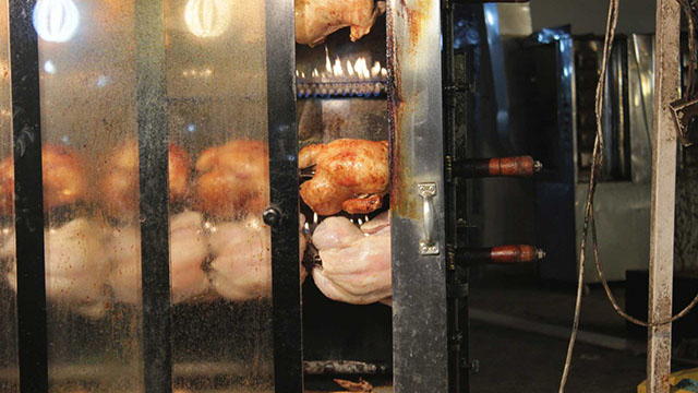 Whole chickens slowly turn on a rotisserie at a makeshift food stand on the street at the Karrada market in central Baghdad.