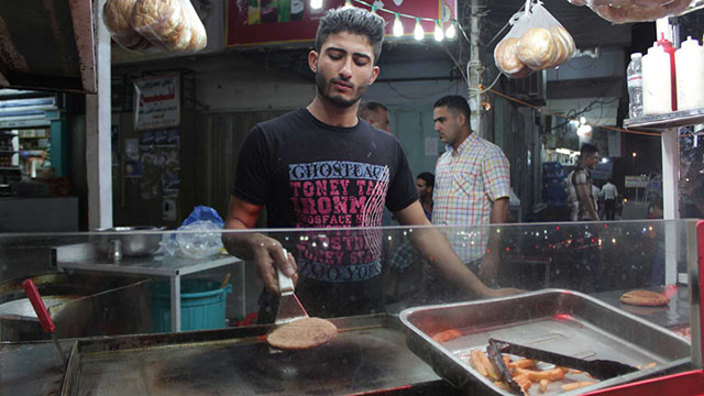 A food vendor flips a burger on a portable grill at the market where he is doing steady business after Iraqis observing Ramadan break their fast.