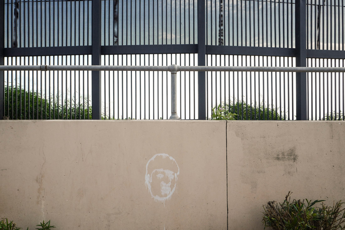 A caricature of Donald Trump spray-painted onto a wall in Hope Park, where a long stretch of fence stands between residents and the border.