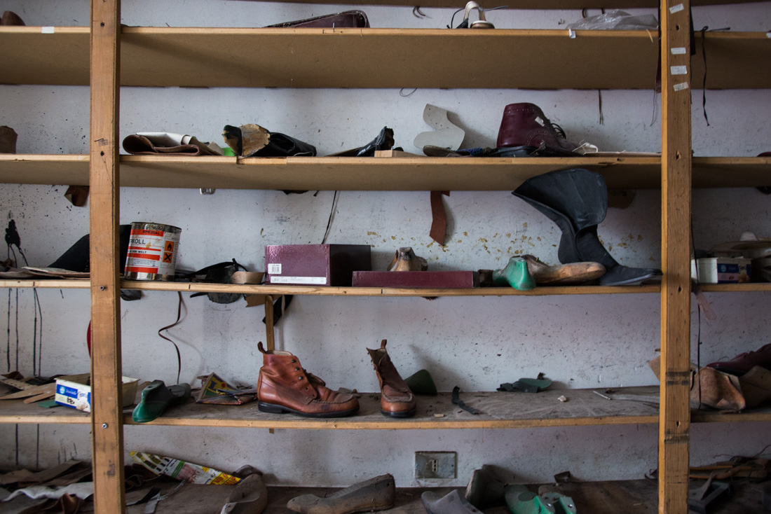 Shoes lie scattered across shelving in a former shop.