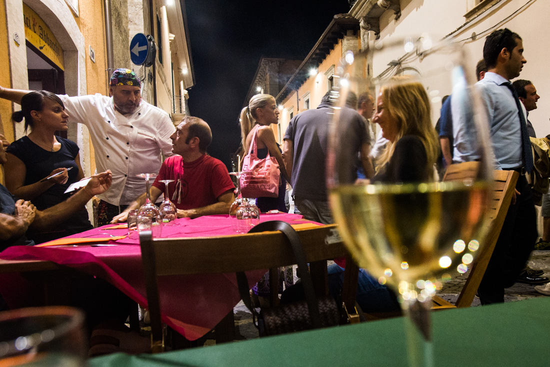 People dine al fresco on a Saturday night in L'Aquila.