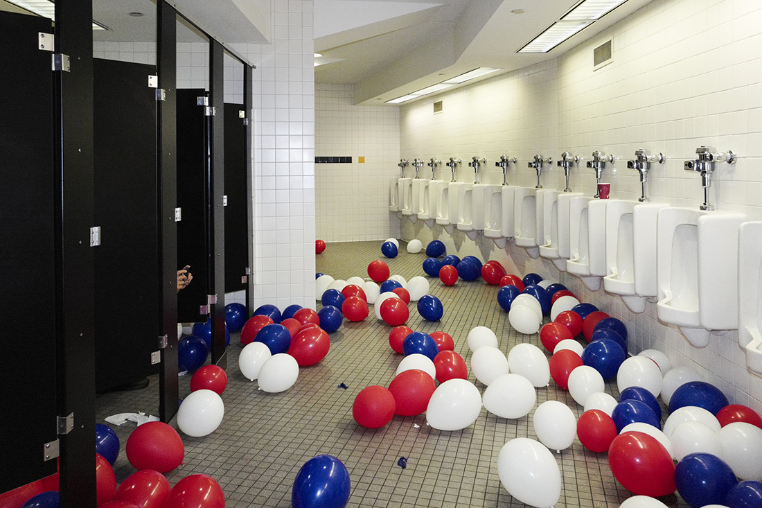 A man in a bathroom stall photographs balloons at the end of the Republican convention.