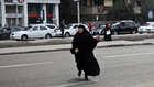 امرأة مصرية تعبر شارعا قريبا من مظاهرة لأنصار حركة الإخوان المسلمين في مصر الجديدة بالقاهرة