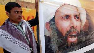 يمني يرفع صورة رجل الدين الشيعي نمر النمر، بعد صدور حكم الإعدام بحقه في تظاهرة أمام السفارة السعودية بصنعاء 18 أكتوبر/ تشرين الأول 2014