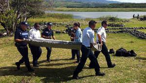 رجال شرطة يحملون جزءا من حطام طائرة عثر عليه على شواطئ جزيرة فرنسية في المحيط الهندي، 29 يوليو/ تموز 2015