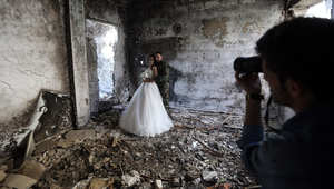 زوجان من سوريا يلتقطان صور زفافهما في مبنى تضرر بشكل كبير من الحرب المدمرة في حمص