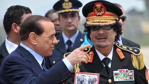 العقيد معمر القذافي الزعيم الليبي السابق في زيارة لروما عام 2009، وبرلسكوني في استقباله