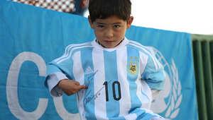 الطفل مرتضى أحمدي يلعب الكرة مرتديا قميص ميسي المصنوع من كيس للقمامة