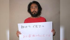 """بالفيديو: صحفي ياباني يحمل لافتة """"ساعدوني"""" في سوريا"""