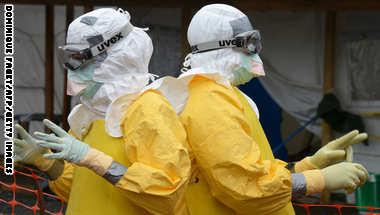 عاملا إغاثة طبية يرتديان أقنعة وملابس واقية في مستشفى تديره منظمة أطباء بلا حدود في منروفيا