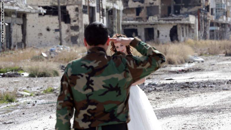 زوجان سوريان يلتقطان صور زفافهما في أطلال مدينة حمص GettyImages-508691258