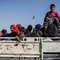 لاجئون سوريون يعبرون الحدود التركية عائدين إلى بلدة تل أبيض في الرقة بعد استعادتها من قبل القوات الكردية في 22 يونيو/ حزيران 2015