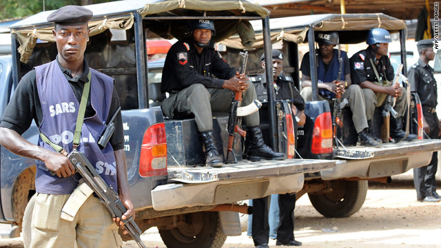 Policemen stand guard at the police headquarters in Jos, Nigeria,  on March 10, three days after the massacre.