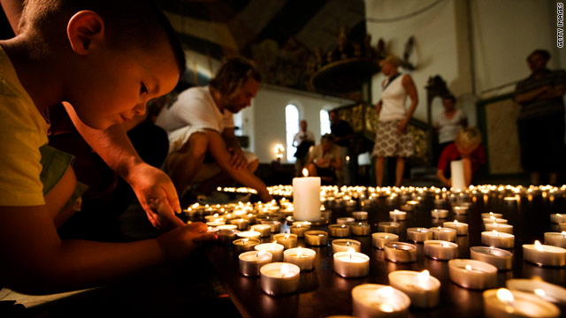 A boy lights a candle inside Oslo Cathedral on July 28 to honor the 76 victims of the attacks in Oslo and Utoeya island.