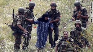 جنود سوريون يحيطون بامرأة كانت تحاول أن تعبر الحدود إلى لبنان الأسبوع الماضي