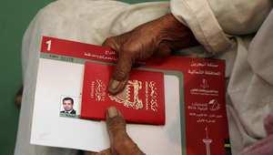 بحريني يحمل جواز سفره للمشاركة في الانتخابات