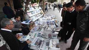 مصريون يطالعون عناوين الصحف لدى بائع على الرصيف في أحد شوارع القاهرة